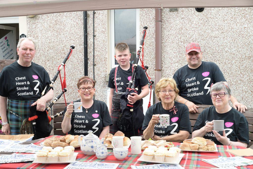 street gathered round a table - Scottish News