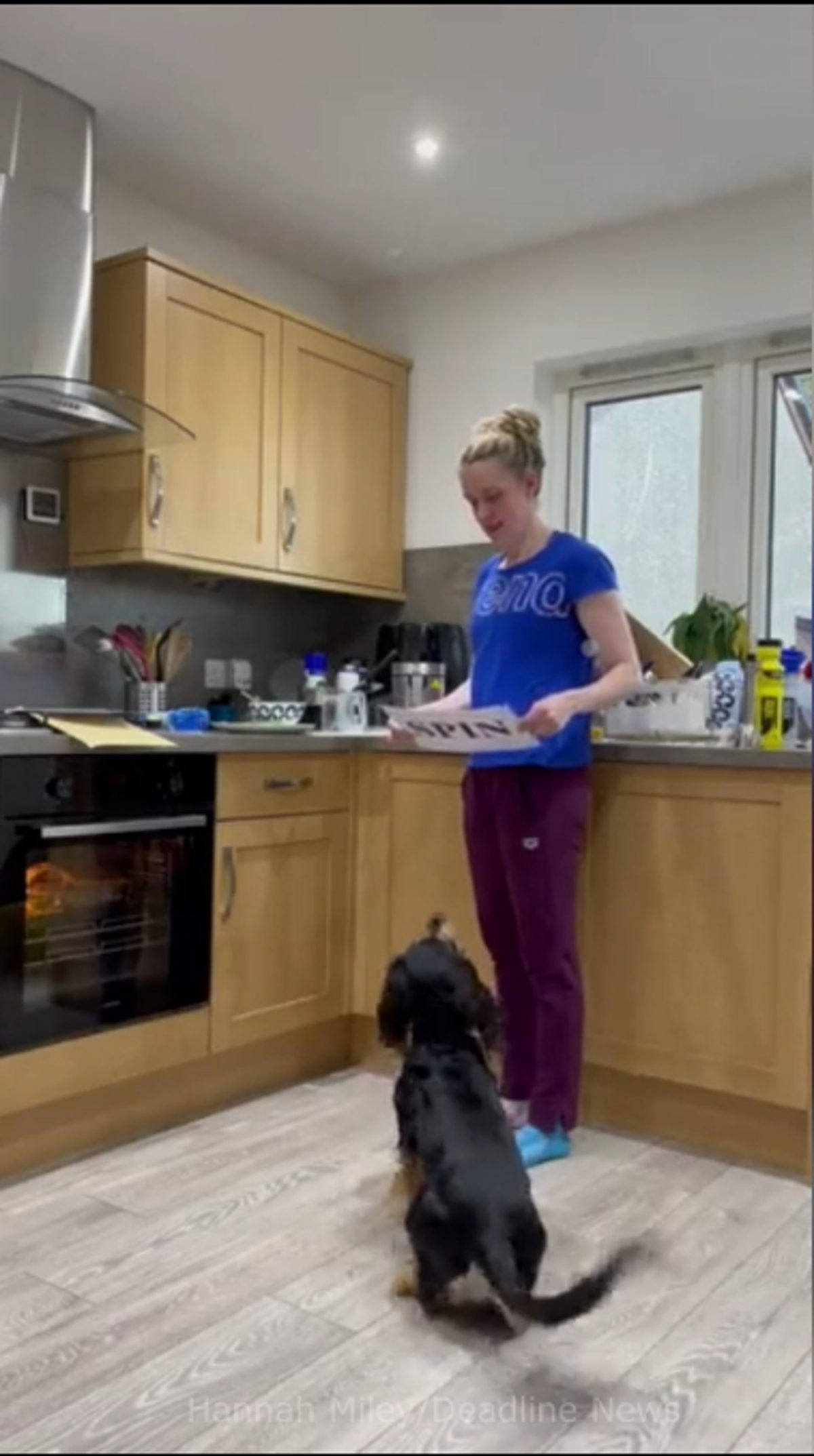Hannah Miley teaching her dog Poppy - sat in front of her - how to read signs.