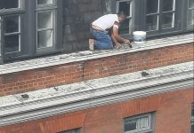 An image of the painter working on the window ledge of a five-storey building.