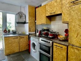 The kitchen in the bungalow, whose cabinets look like they are composed of plywood.
