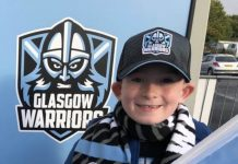Harry Jack beside Glasgow Warriors sign